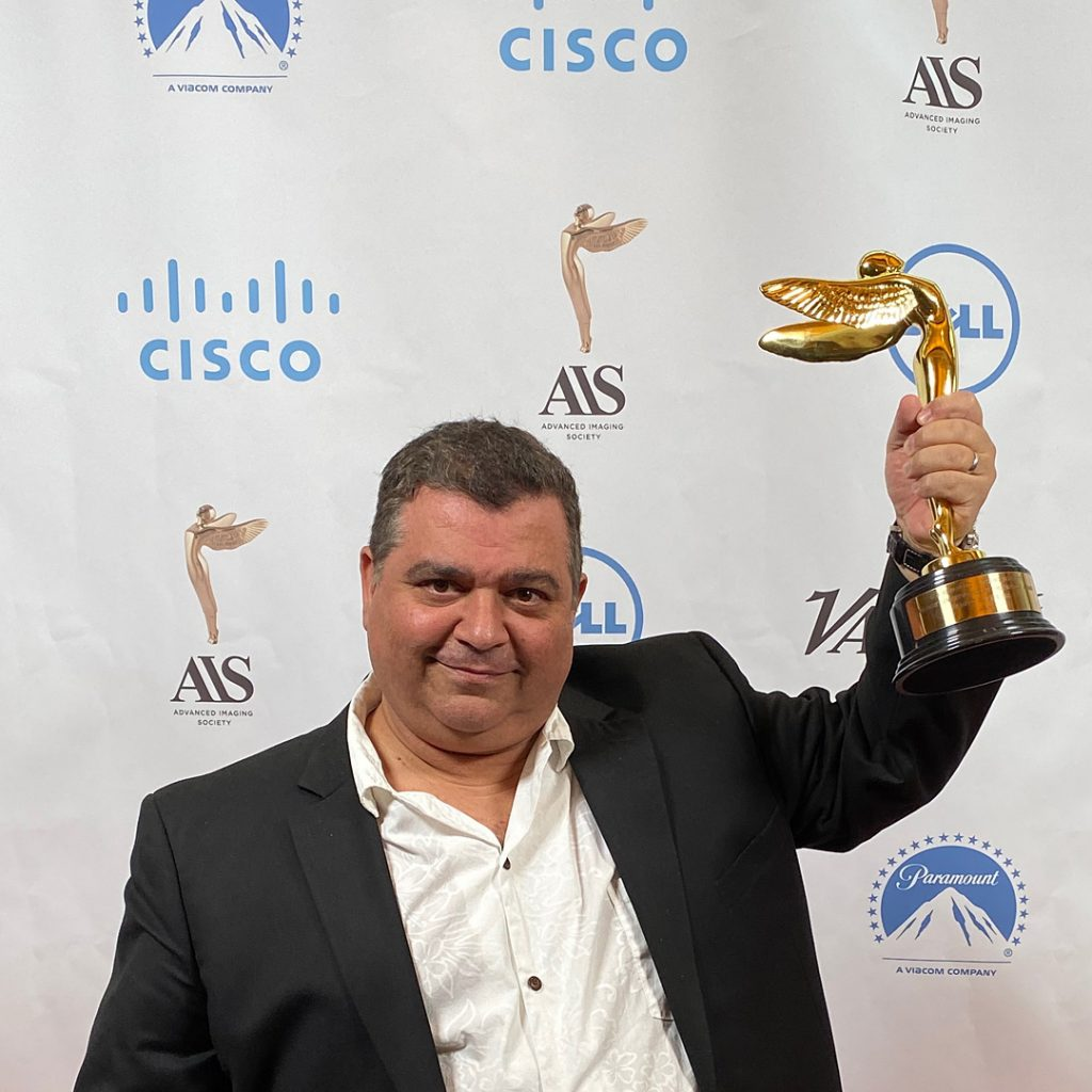 Hawkeye Systems Senior Technology Advisor Michael Mansouri accepts a 2019 Lumiere Award from the AIS